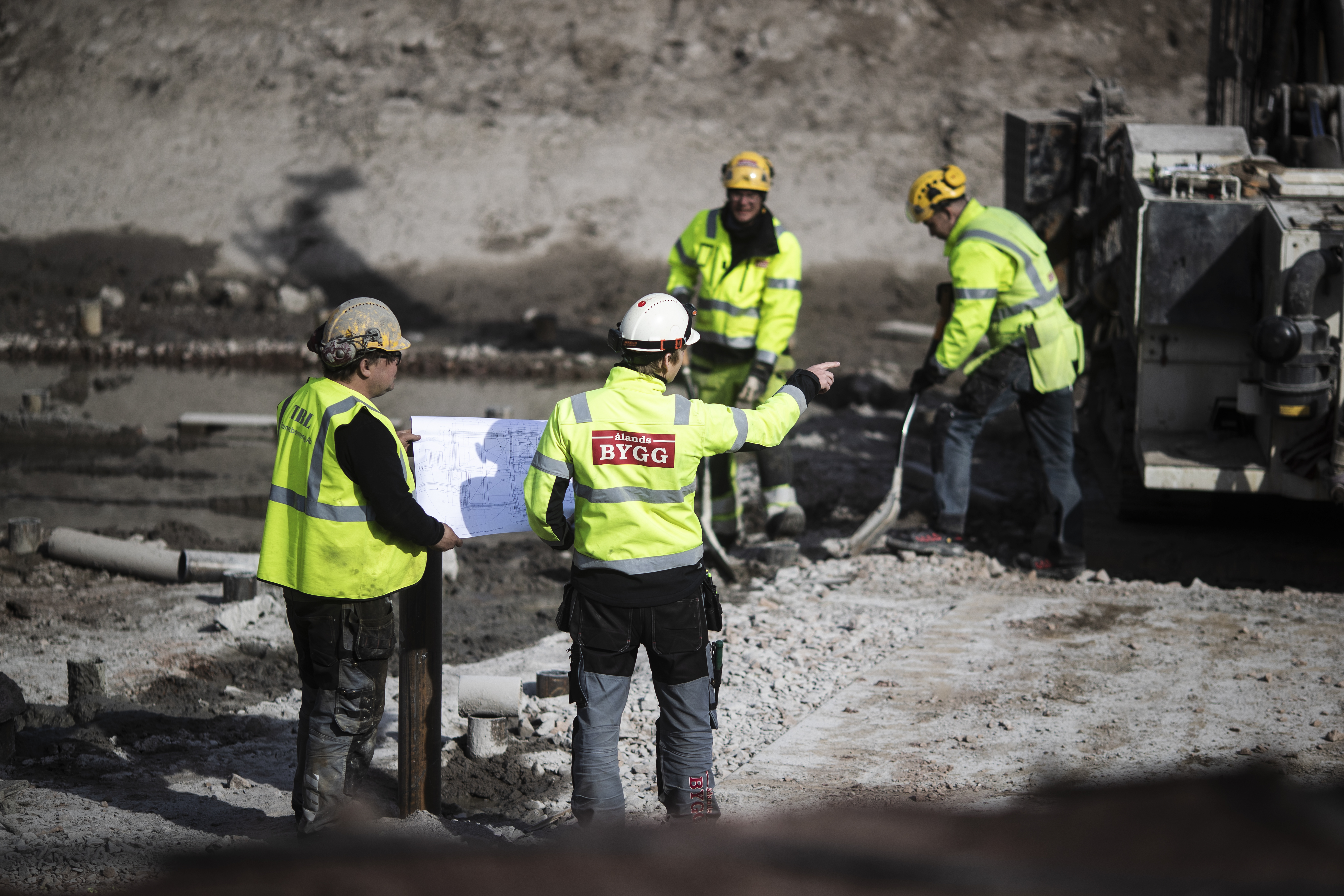 Fyra byggarbetare står utomhus
