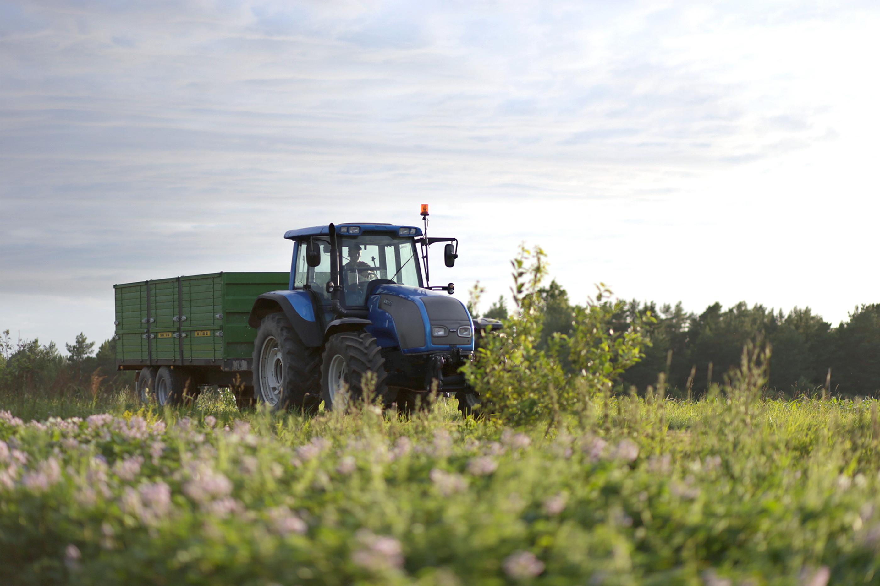 Traktor med släp som kör på åker