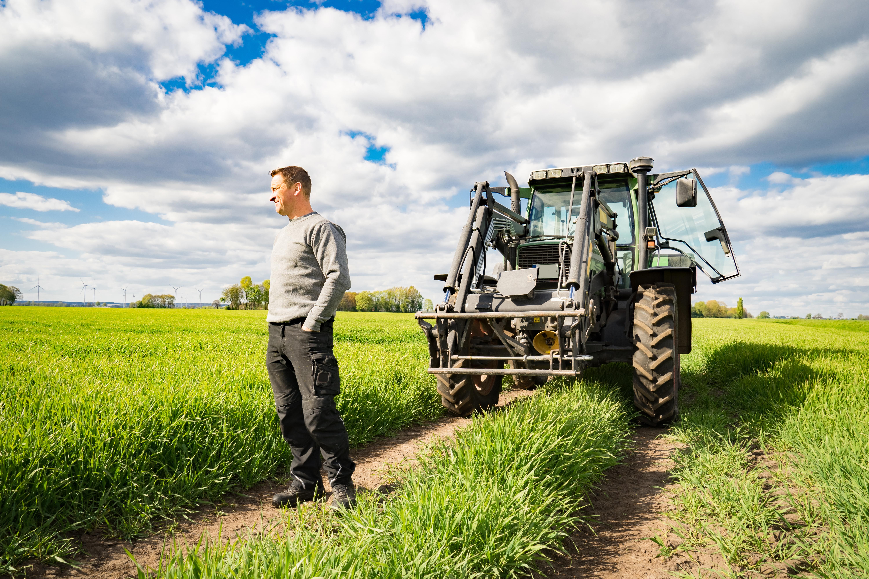 Man står på en åker bredvid sin traktor