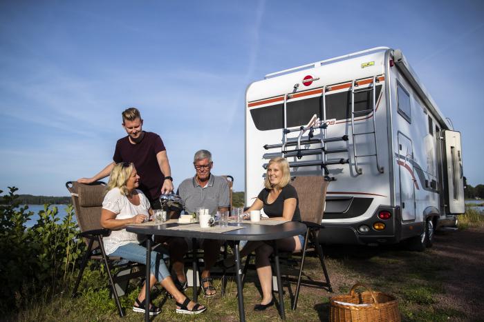 Familj sitter utanför sin husbil