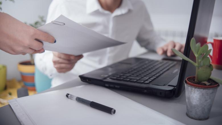 Man som sitter vid ett bord framför en dator och får ett papper