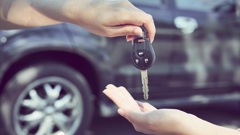 En hand som ger en bilnyckel till en annan hand