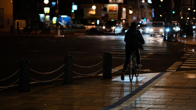 Cyklist som cyklar i mörk stadsmiljö utan reflex