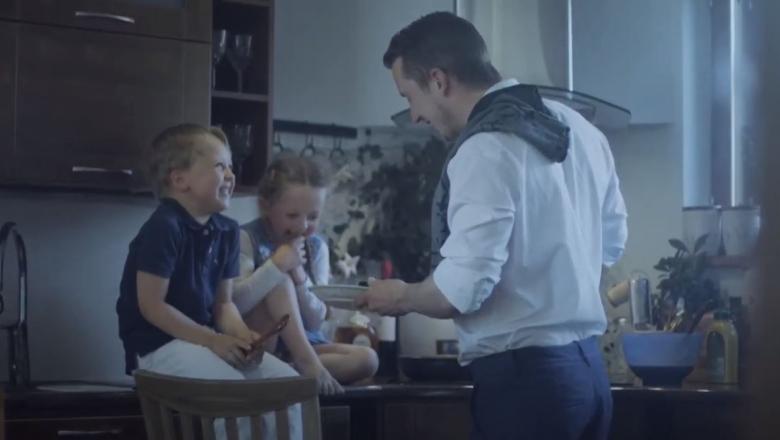 Pappa med två barn vid spisen
